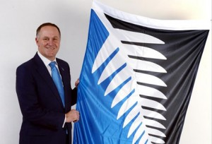 "Prime Minister John Key poses with the victorious Kyle Lockwood design ""Burnt Weetbix: A New Zealand Story of Flag"""