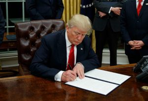 "PICTURED: President Trump signs an executive order he says is ""some piece of paper or something."""