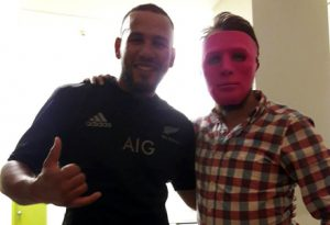 An unwitting tourist with cultural facemask takes a picture with a man he sincerely believes to be an All Black.